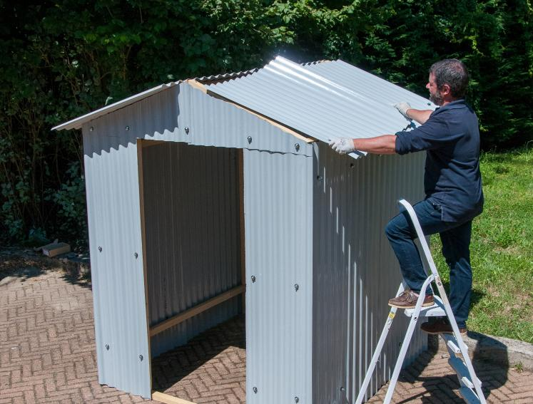 Man building small workshop shed with ONDUPLAST COLOUR roof sheets