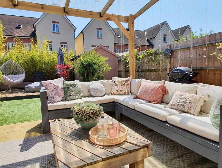 Outdoor seating area with pergola, made from clear roofing sheets, and outdoor furniture