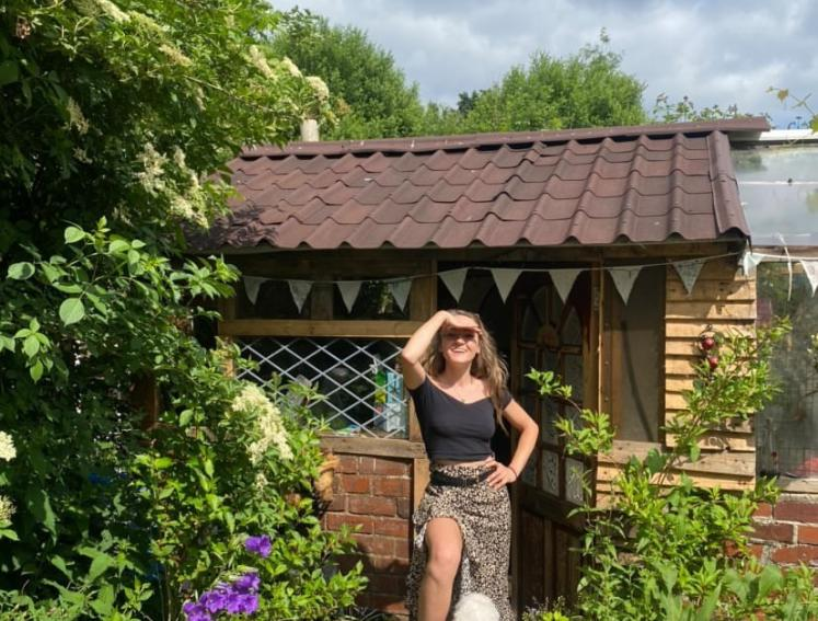 Woman in front of allotment shed built with Onduline ONDUVILLA tile look roofing