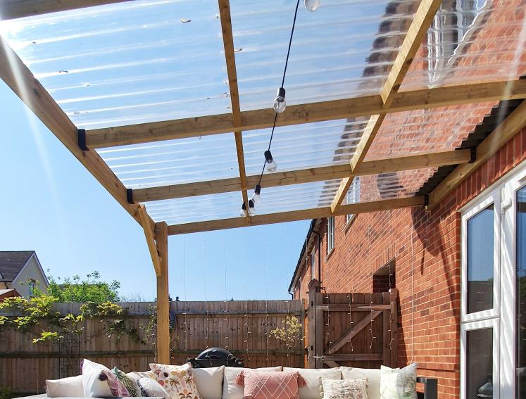Outdoor seating area with pergola made from timber and Onduline clear roofing sheets